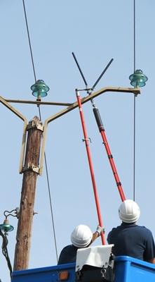 """Le vissage des """"bougies"""" s'effectue à distance d'au moins 0,60 m à cause des 20 000 volts de la ligne (photo MN)"""